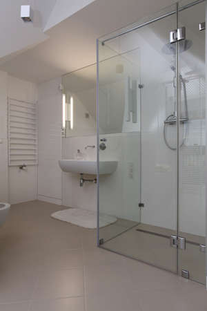 Bright modern bathroom with glass shower Imagens