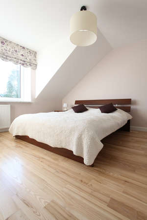 Huge wooden bed in bright spacious bedroom