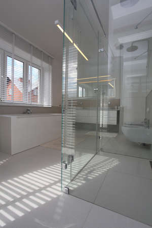 Glass bathtube in modern and bright bathroom photo