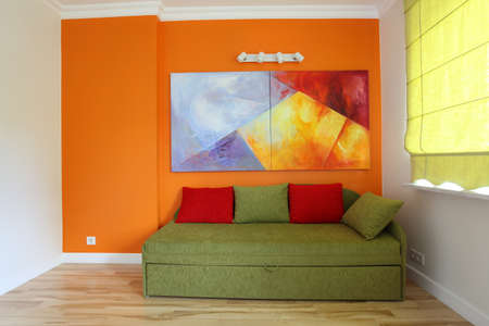 Orange wall and green sofa in teenage room photo