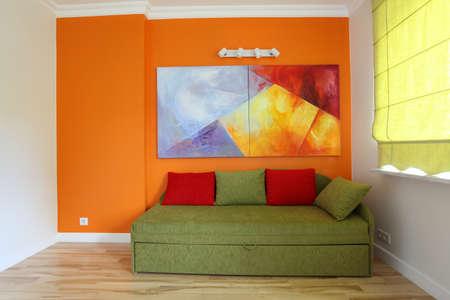 sofa bed: Orange wall and green sofa in teenage room Stock Photo