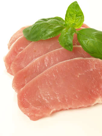 Slices of pork with basil leaves on isolated background. Stock Photo - 15611854