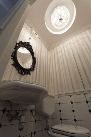 Old fashioned toilet with original huge chandelier photo