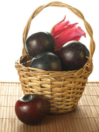 Wicker basket with big tasty plums, isolated photo