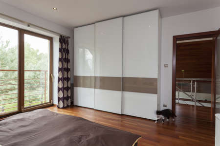 Contemporary bedroom with balcony and huge wardrobe photo