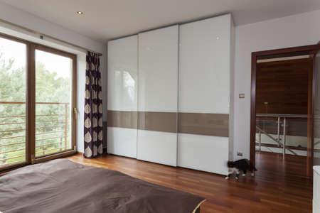 contemporary bedroom: Contemporary bedroom with balcony and huge wardrobe