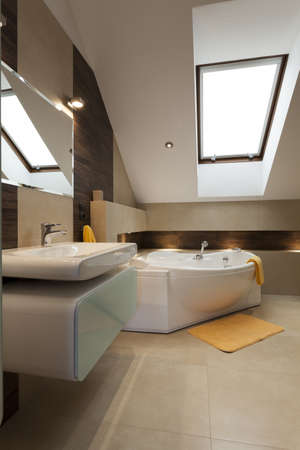 additions: Modern bathroom with yellow additions in the attic Stock Photo