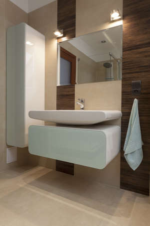 Elegant washbasin, shelf and mirror in bathroom photo