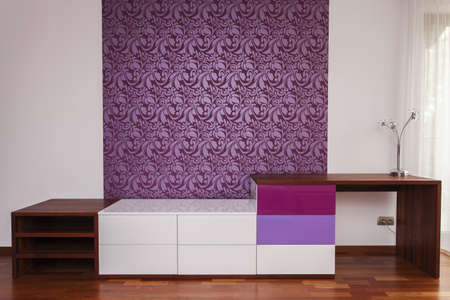 Modern commode in stylish violet and white room with design on a wall Stock Photo - 15784266