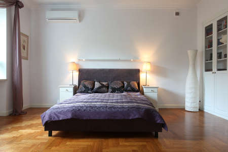 bedroom design: Stylish white bedroom with a purple bed
