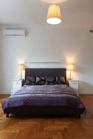 Vertical view of bedroom with violet bed