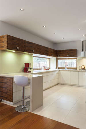 Vertical view of modern kitchen with white counter top photo