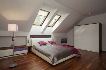 Bright bedroom with wooden floor and violet additions Stock Photo - 15810600