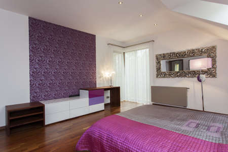 Violet bedroom with patterned wallpaper on one wall photo