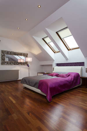 Spacious bedroom with purple and silver bed  photo