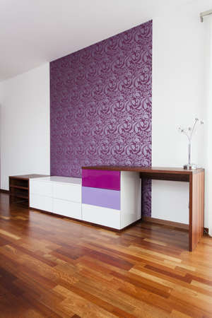 Room with patterned violet wallpaper and commode photo