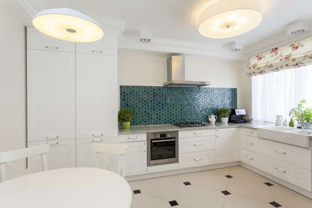 wood blinds: White kitchen interior with turquoise tiles