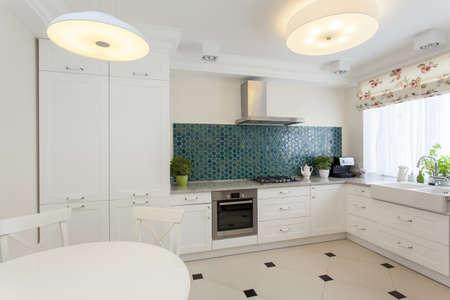 interior designer: White kitchen interior with turquoise tiles