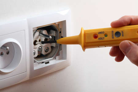 inspection: Checking voltage with detector in power socket