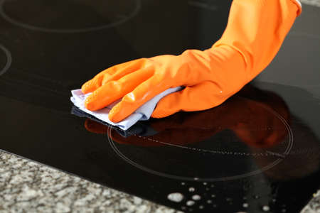 Closeup of hand in glove cleaning a stove Stock Photo - 16137774