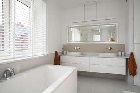 cabinets: Interior of spacious, plain and white bathroom