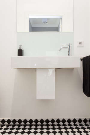 Plain white wash basin in modern elegant bathroom photo