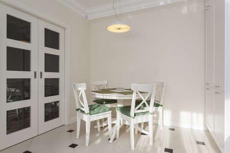 jídelna: Kulatý bílý stůl ve světlé a moderní kuchyni Reklamní fotografie