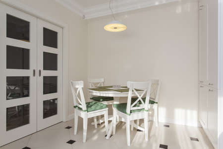 dining table and chairs: Round white table in bright and modern kitchen