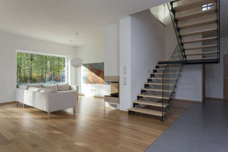 Spacious living room and wooden staircase photo