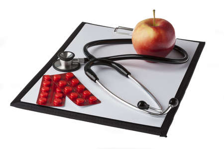 ilness: Stethoscope, drugs and apple on notepad, isolated background