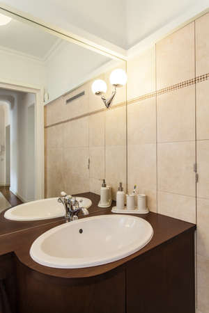 well equipped: Elegant washbasin and huge mirror in stylish bathroom