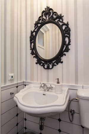 well equipped: Elegant white sink and oval mirror in toilet