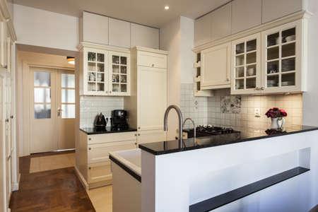 cocina antigua: Cocina con estantes y paredes blancas cremosas