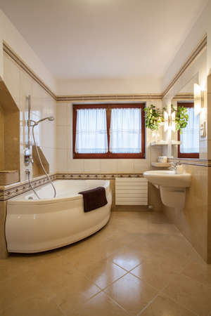Beige bathroom with big bath and window photo