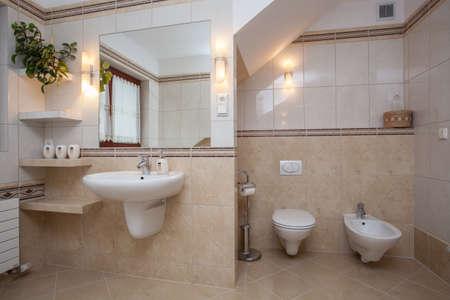 bidet: Interior of creamy bathroom, sink, toilet and bidet Stock Photo