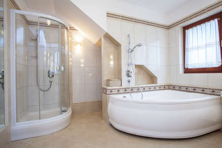 Shower and big bath in beige bathroom interior Stock Photo