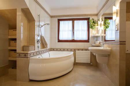 Contemporary bathroom interior, big bath and window photo