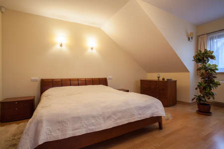 Big wooden bed in bedroom on the attic photo