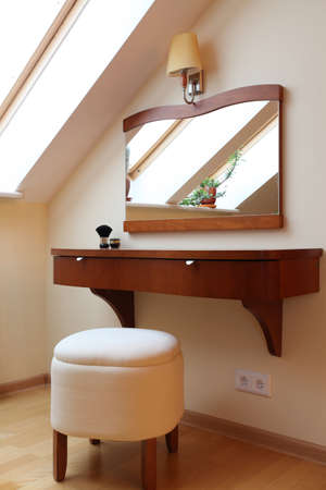 Wooden dressing table with mirror on the attic photo