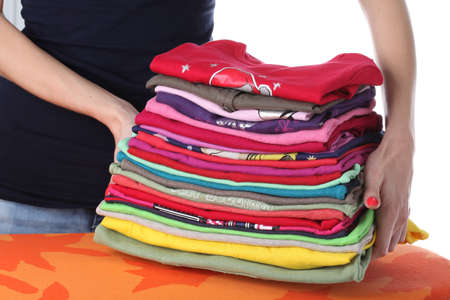 Woman raising up coloured pile of clothes Stock Photo - 16685373