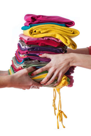ironed: Heap of ironed washed clothes giving from hand to hand Stock Photo