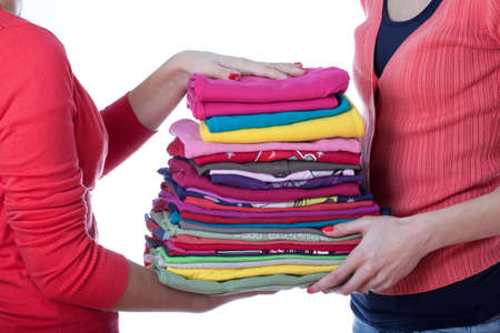 homemakers: Two homemakers with heap of colorful ironed washind