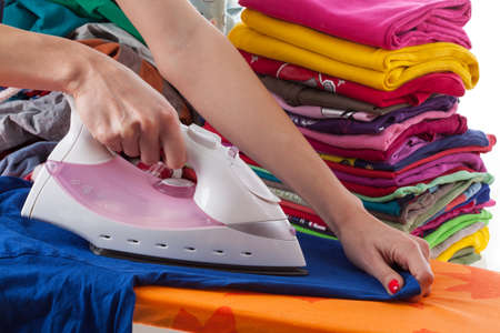Woman ironing T-shirt on orange ironing board photo