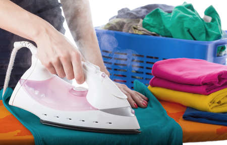 Woman ironing clothes with a steaming iron photo
