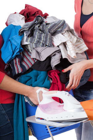Women passing each other a heap of laundry. Stock Photo - 16756043