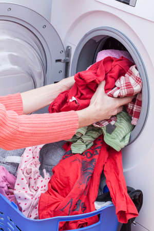 Womans hands putting clothes into washing machine photo