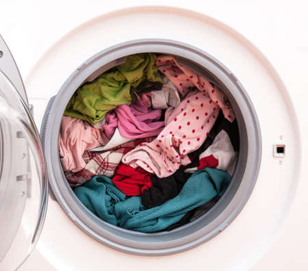 Washing machine full of dirty clothes, closeup photo