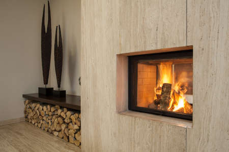 travertine house: Travertine house  burning fireplace and pieces of wood Stock Photo
