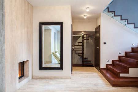 travertine house: Travertino casa: espejo enorme y escaleras de madera