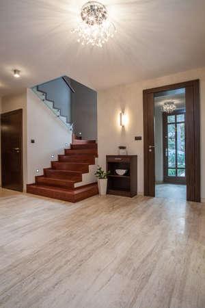 travertine house: Travertino casa: escaleras de madera y vidrio de entrada